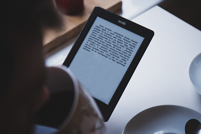 A person reading a Kindle Paperwhite while drinking a coffee